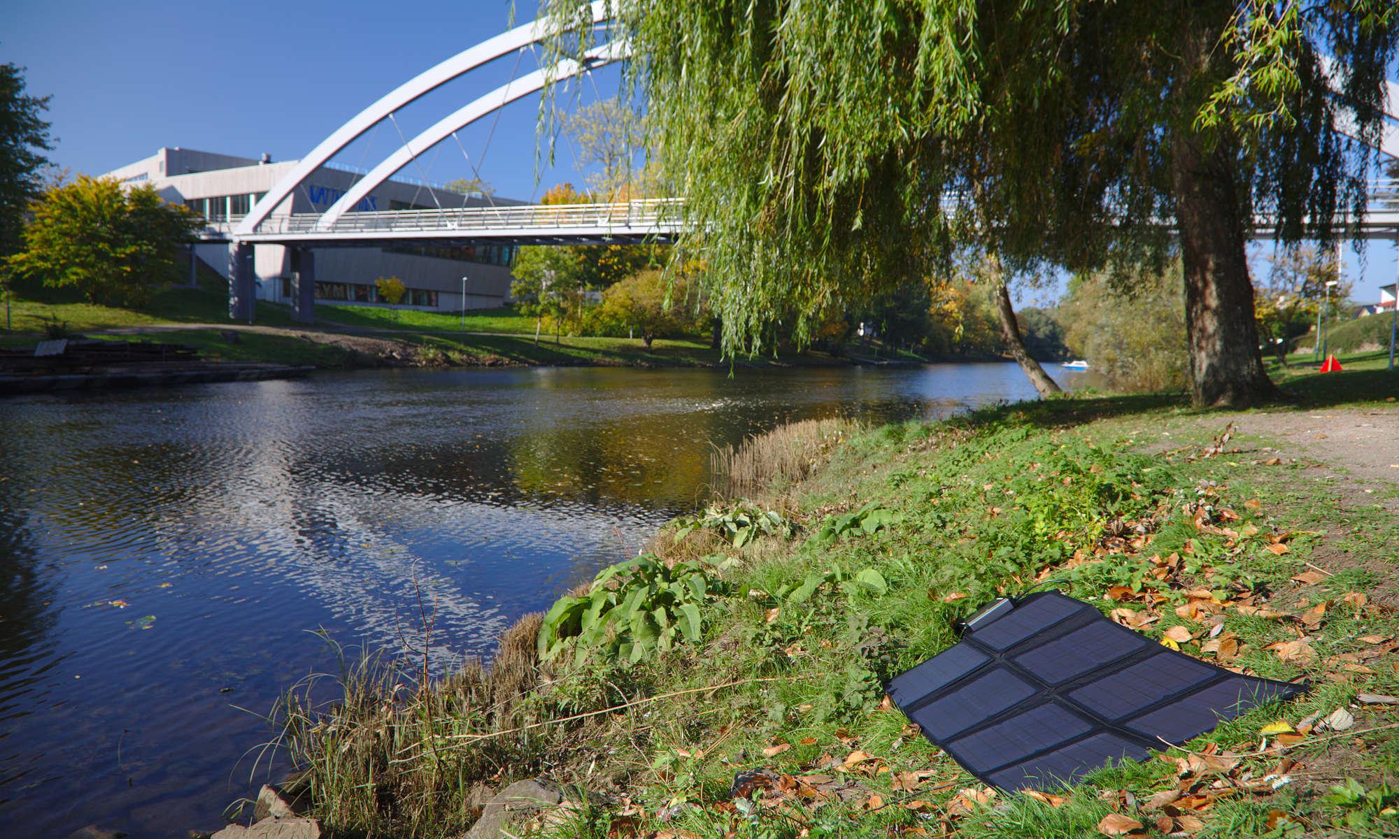 Polaroid vikbara solceller SP100 på gräset bredvid Rönne å