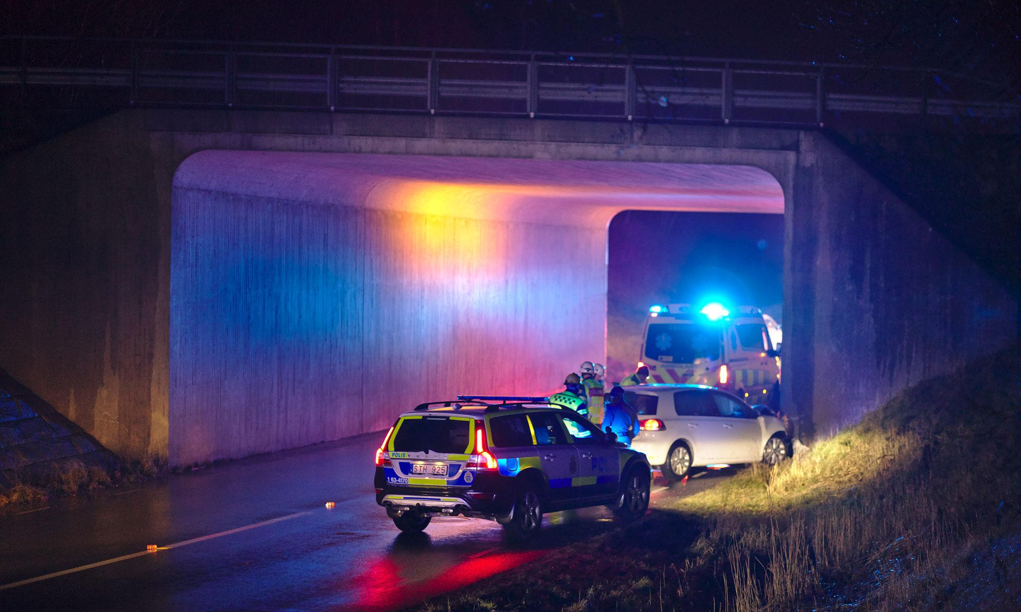 Vit personbil har kört in i bro och polis och ambulans är på plats