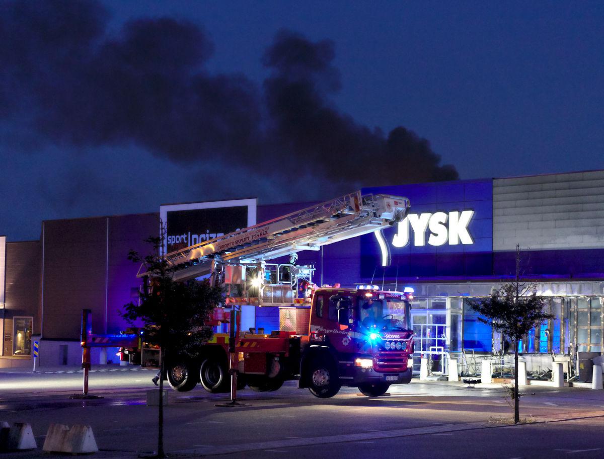 Brandbil framför brandhärjade Jysk i Ängelholm och med ytterligare en rökpelare i bakgrunden